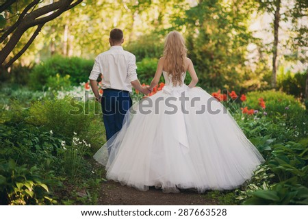 The bride and groom are in the park holding hands around the beautiful flower beds of poppies and white flowers - stock photo