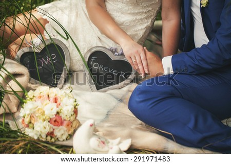 The bride and groom are sitting on the plaid in nature