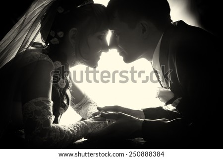 The bride and groom are sitting opposite each other. - stock photo