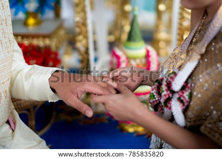 the bride and groom exchange rings. Wedding ceremony in thailand.