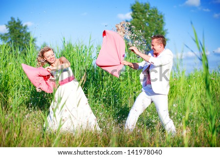 The bride and groom fooling around in the nature. Pillow fight in the grass.