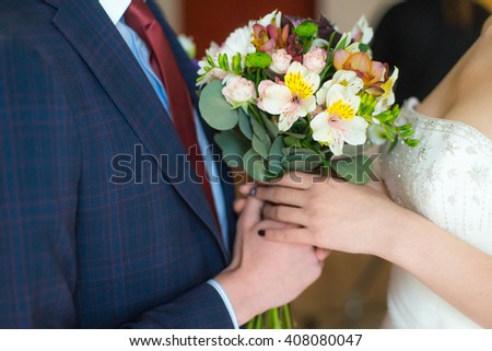 The bride and groom hold each other's hands. Hands of the newlyweds with wedding bouquet.