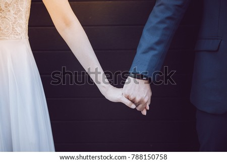 The bride and groom hold hands together.