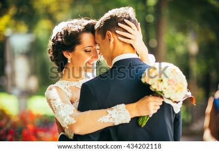 The bride and groom hugging and kissing near a tree and cars in town. Sensual and emotional photo. Sunny day. Love couple. Smile bride. Attractive groom.  - stock photo