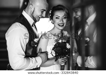 The bride and groom in a cozy house, photo taken with natural light from the window. - stock photo