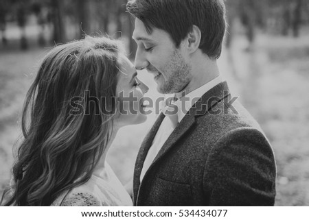 The bride and groom in a forest. Man and woman kissing in the woods. Close-up.