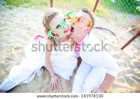 The bride and groom in a funny glasses sitting on the sand near the gate for beach football. Laugh, joke, fun, smile, fool around. - stock photo