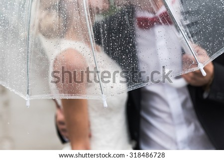 the bride and groom in the rain are covered with a transparent umbrella, rain drops - stock photo