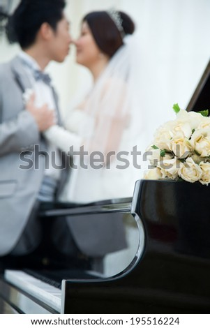 The bride and groom kiss in front of the piano  - stock photo