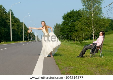 The bride and groom on road waiting for a car