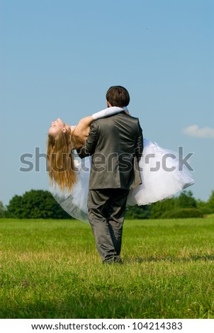 The bride and groom on their wedding day in a field