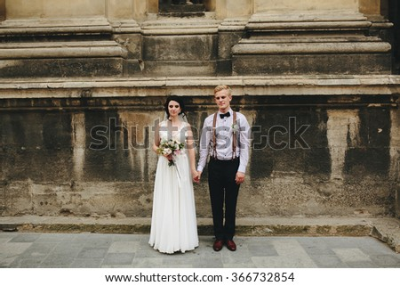 The bride and groom posing in the old street, family photo - stock photo