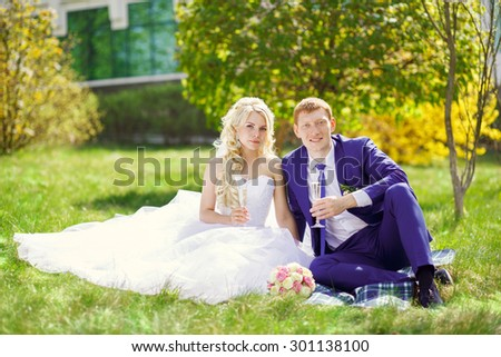 the bride and groom sit on the grass in the park, with glasses in their hands. - stock photo