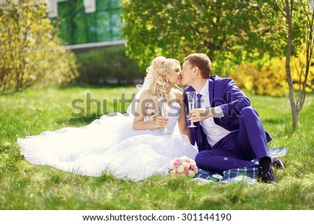 the bride and groom sit on the grass in the park, with glasses in their hands and kiss. - stock photo