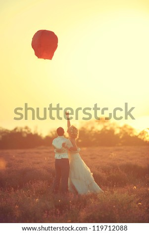 the bride and groom start a Chinese lantern in the wild lavender field - stock photo