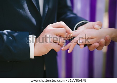 The bride and groom wear each other at a wedding ceremony when rings on a background of multi-colored ribbons, love, marriage, relationships