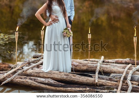 the bride and groom with wedding bouquet on the river - stock photo