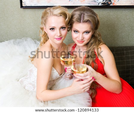 The bride and her bridesmaid with a glass of wine on the sofa