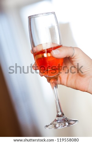 The bride are drinking pink champagne while getting dressed. - stock photo