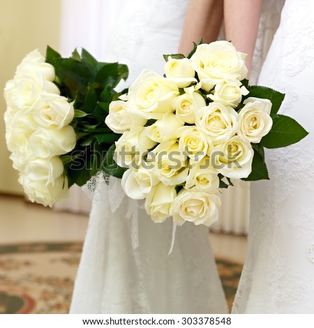 The bride at a wedding holding a bouquet of flowers. The bride in a white dress at a wedding ceremony with a bouquet of roses. - stock photo