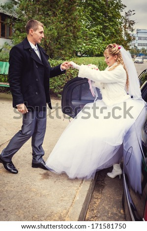 The bride comes out from the car with man's help. Happy bride and groom out of wedding limousine - stock photo