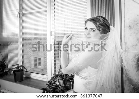 The bride hiding her face behind a veil
