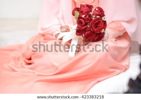 the bride holding a bouquet of red flowers