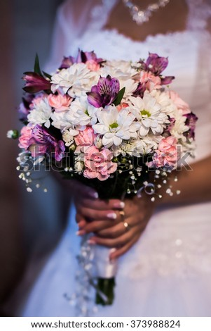 the bride holding a bouquet of white, pink and mauve flowers, women's hands and a bouquet of flowers, the morning of the bride, wedding flowers - stock photo