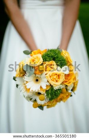 the bride holding a bouquet of yellow - stock photo