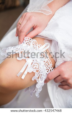 The bride holds the white lace garter in the studio