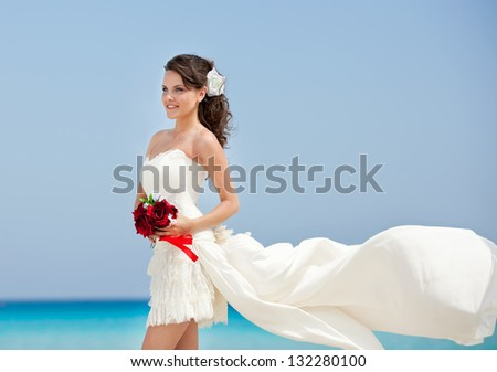 the bride in dress with wedding bouquet on the beach. - stock photo