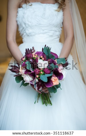 The bride is holding a wedding bouquet of beautiful flowers
