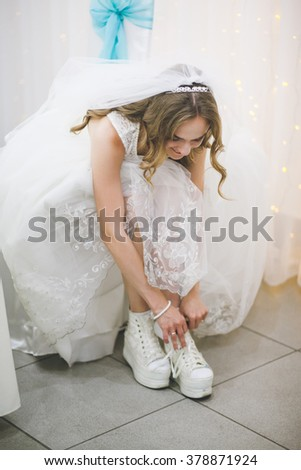 The bride is putting on her shoes for the wedding day.