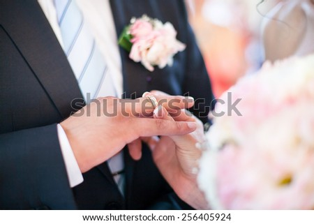 The bride puts a wedding ring on groom's finger. Blurred visible blue tie, boutonniere, wedding pink bouquet. Gentle colors. - stock photo