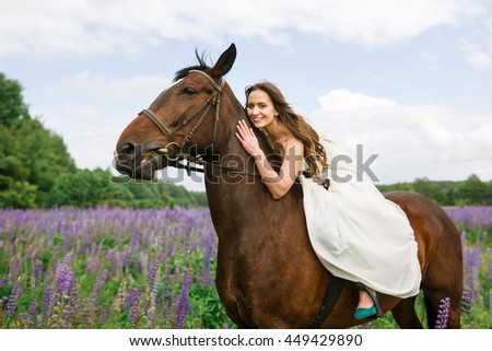 The bride riding on horseback across a field of lupine