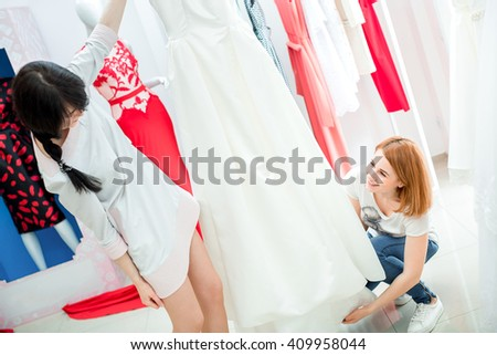 the bride selects the wedding dress in the Studio. a young woman chooses a white dress in the store. salon	 of wedding dresses - stock photo