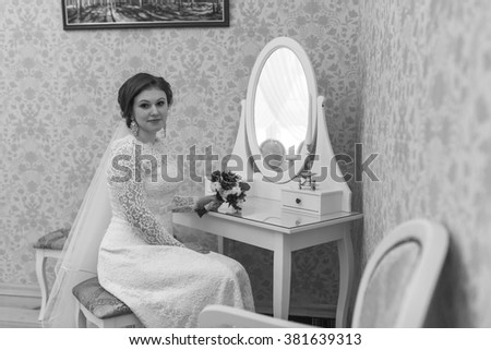 The bride sits on a chair and looking at vintage mirror