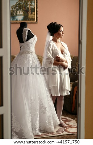 The bride stands near wedding  dress in the room