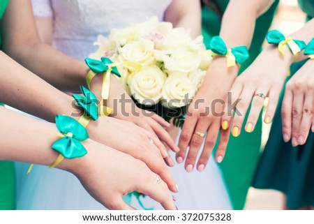 the bride with a bouquet and hands of bridesmaids with green bracelets - stock photo