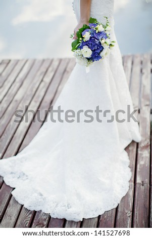 the bride with a bouquet from blue and white flowers; wedding concept - stock photo