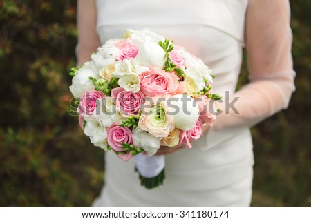 The bride with a bouquet of spring is in the park. Bouquet of pastel-colored roses. Those girls are not seen. We see the bride's dress and the delicate bouquet. Background, copy space.