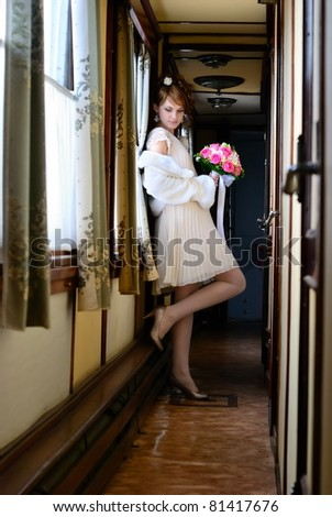 The bride with a bunch of flowers in a corridor of the ancient wagon