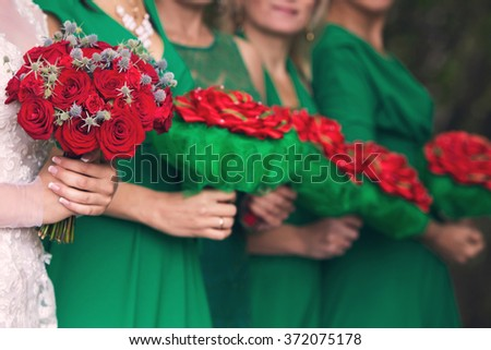 the bride with a red bouquet of roses and bridesmaids with red bouquets in hands - stock photo