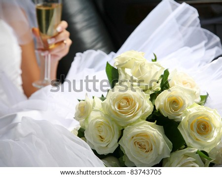 The bride with a wedding bouquet and champagne in a car - stock photo