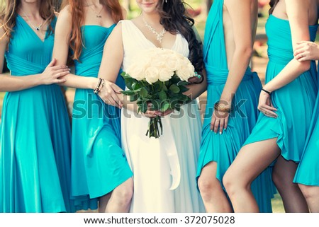 the bride with a white bouquet of roses and bridesmaids in blue dresses - stock photo