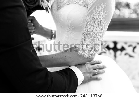 the bridegroom embraces the bride's waist close-up. black and white image