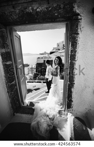 The brides stand near door  on the seashore