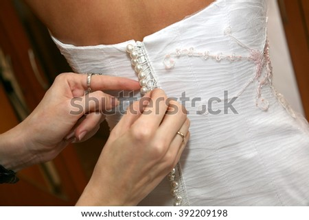 the bridesmaid helps fasten buttons on the dress the bride - stock photo