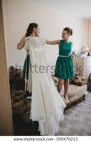The bridesmaids keep a wedding dress