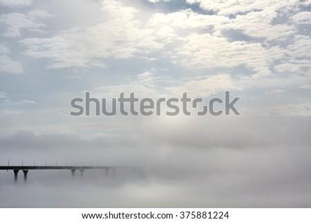 the bridge goes into the morning mist fog - stock photo